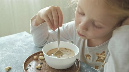 aveia : Little cute girl eats oatmeal with nuts and dried fruits for breakfast. Healthy food concept Stock Footage