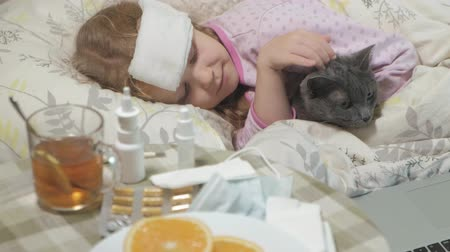 caring : Sick girl with a temperature. A child with fever is lying in bed with a cat.