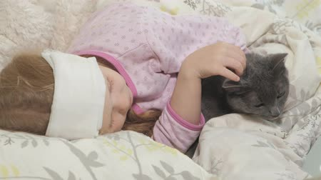 termometr : Sick girl with a temperature. A child with fever is lying in bed with a cat.