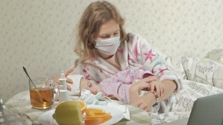 термометр : Sick girl with a temperature. Child with fever is lying in bed with her mother, eating fruit and using a laptop.