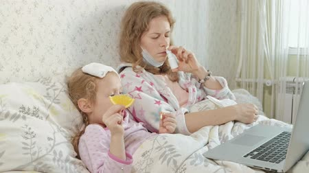 cama : Sick girl with a temperature. Child with fever is lying in bed with her mother, eating fruit and using a laptop.