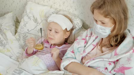 во : Sick girl with a temperature. Child with fever is lying in bed with her mother, eating fruit and using a laptop.