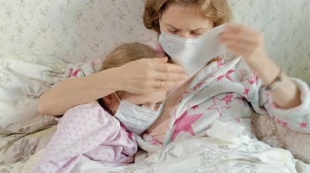 温度計 : Sick girl with a temperature. Child with fever is lying in bed with her mother, eating fruit and using a laptop.