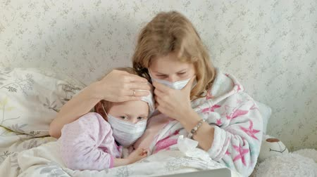 猫 : Sick girl with a temperature. Child with fever is lying in bed with her mother, eating fruit and using a laptop.