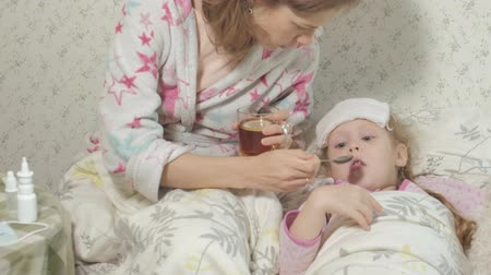 заботливый : Sick girl with fever. Child with fever: a woman caring for a child and medicating