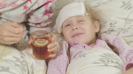 horečka : Sick girl with fever. Child with fever: a woman caring for a child and medicating