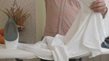 tahy : A man strokes his shirt on the ironing board in his house