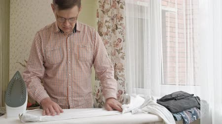 гладильный : A man strokes his shirt on the ironing board in his house