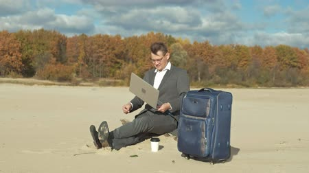 bavul : Businessman with a laptop suitcase working relaxing on the beach Stok Video