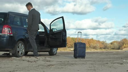 his : Businessman with a laptop suitcase working relaxing on the beach near his car.