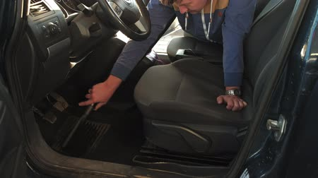 myjnia samochodowa : Handyman vacuuming car back seat with vacuum cleaner