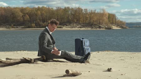 чемодан : Businessman with a laptop suitcase working relaxing on the beach Стоковые видеозаписи