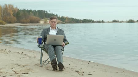 yakın : Mature businessman sitting and relaxing near a river. Man in suit and using laptop.