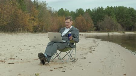 река : Mature businessman sitting and relaxing near a river. Man in suit and using laptop.