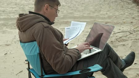 река : Mature businessman sitting and relaxing near a river. Man in a warm jacket and using laptop. Стоковые видеозаписи
