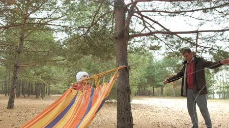 hang : A young man in the woods sets hammock. Daughter walks nearby.