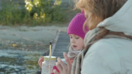 cold drinks : little girl, in warm clothes, sits on the bank of the river, on the river port, drinks hot tea, picnic