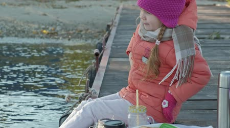 oturur : little girl, in warm clothes, sits on the bank of the river, on the river port, drinks hot tea, picnic