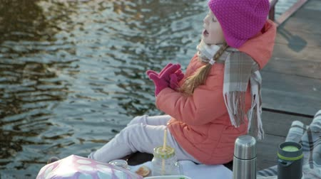 senta : little girl, in warm clothes, sits on the bank of the river, on the river port, drinks hot tea, picnic