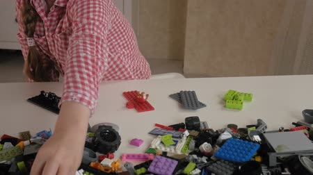 construtor : The little girl builds from the designer cubes. The joy of games