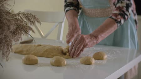 yaşlılar : Happy senior woman rolling pizza dough at home in the kitchen Stok Video