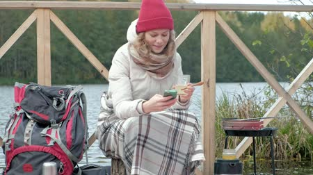 trave : A woman tourist in warm clothes on the bridge near the river bank with a backpack, covered with a rug, drinking hot tea from a mug, using a telephone, cooking food on a grill, picnic, a dog playing nearby, outdoor activities and a healthy lifestyle. trave