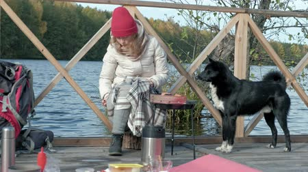 inspirar : Woman tourist in warm clothes on the bridge by the river bank with a backpack, preparing sausages on the grill, picnic, sitting next to a dog, active leisure, healthy lifestyle. Travel concept