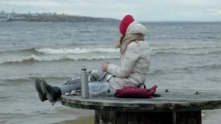 kufel : young woman in warm clothes sitting on the ocean shore, on a wooden coil, drinking hot tea from a bottle, using a telephone, cold weather, a storm Wideo