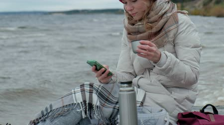 змеевик : young woman in warm clothes sitting by the ocean, on a wooden coil, drinking hot tea from a bottle, using a telephone, cold weather, storm, close-up, portrait
