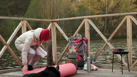 piknik : A woman tourist on the bridge near the river bank takes things out of her backpack, spreads a tourist rug, next to her is a dog, a picnic, outdoor activities and a healthy lifestyle . travel concept
