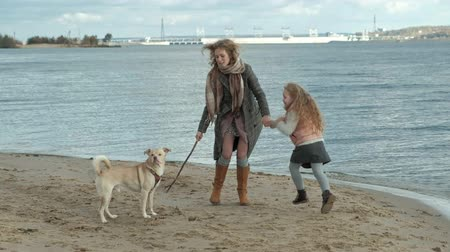 brood : young woman in a coat with a girl with curly hair, mom and daughter, run, play with a brown dog on the beach, brood her stick, cold weather