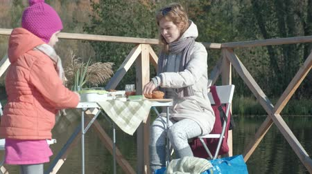 rodičovství : a young woman and a little girl in warm clothes, mother and daughter, had a picnic on the river bank on a wooden bridge, prepare food, the girl feeds the dog, weekends, cold weather, outdoor recreation, tourism
