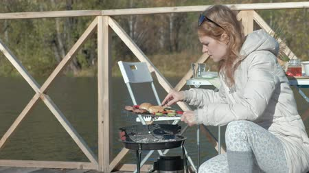 wooden bridge : young woman in warm clothes, preparing vegetables and meat on the grill, preparing a burger, a dog playing nearby, a picnic on the river bank on a wooden bridge, a weekend, cold weather, outdoor recreation, tourism