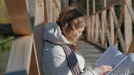 가까운 : a woman on the bridge near the autumn river reads a book and drinks tea