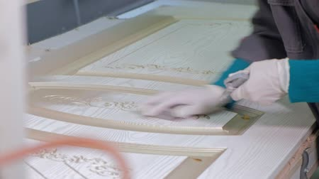 carpintaria : man, the worker makes the effect of aging doors. production of interior doors from wood