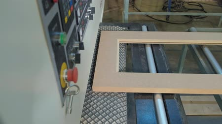 újra : the process of grinding wooden doors on the machine.production of interior doors of wood