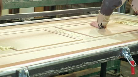 yine : a man, a worker cleans a wooden blank from the dust, a door.production of interior doors of wood Stok Video