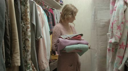 šatník : Beautiful girl smiles and goes over towels on the shelf in her dressing room