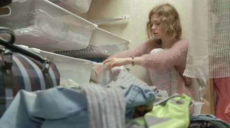 носить : A beautiful girl is depressed, a tired young mother throws out clothes from the baskets in her dressing room. puts things in order