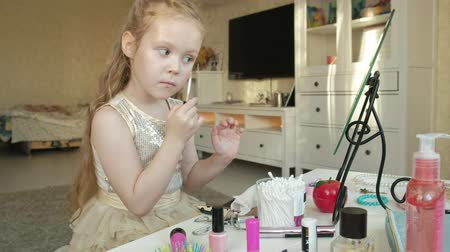 csipesz : a little girl with red hair puts on a concealer, looks in the mirror, makeup, face, fashion, style, cosmetics