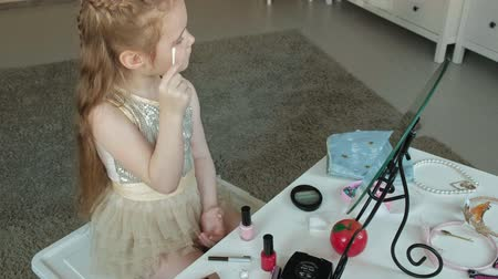 csipesz : little girl with red hair draws eyebrows with eyebrow pencil, looks in the mirror, makeup, face, fashion, style, cosmetics,