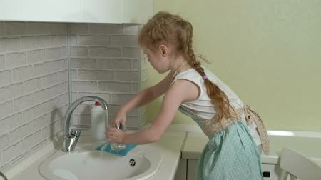 copinho : beautiful little girl in an apron washes a mug in the bright kitchen, helps parents