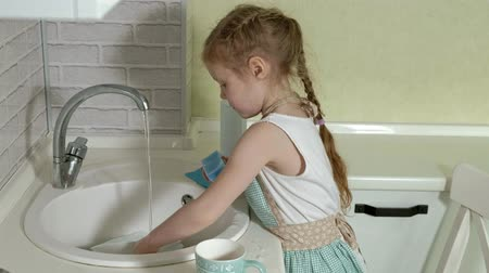 wastafel : beautiful little girl in an apron is standing on a chair, in the bright kitchen, washes a cup with a sponge, helps parents