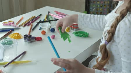 plastelíny : a little girl plays with plasticine, rolls balls, there are figures and colored pencils on the desktop, the development of fine motor skills of hands