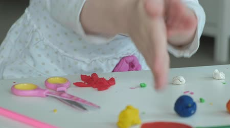 plastelíny : a little girl plays with plasticine, rolls balls with her hands, there are figures and colored pencils on the desktop, the development of fine motor skills of hands