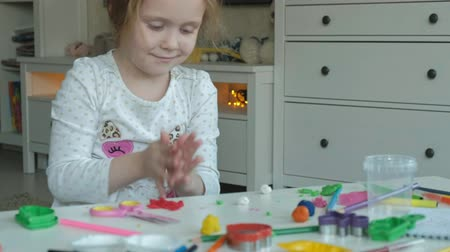 education kids : happy little girl plays with plasticine, rolls balls with her hands, figures and color pencils lie on the desktop, development of fine motor skills of hands