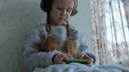 pigtail : happy little girl with pigtails in headphones, uses the phone, plays, smiling, sitting in the room on the windowsill, covering herself with a carpet, close-up hands Stock Footage