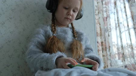 plait : happy little girl with pigtails in headphones, uses the phone, plays, smiling, sitting in the room on the windowsill, covering herself with a carpet