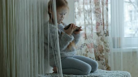 fonat : happy little girl with pigtails, uses the phone, plays, smiling, sitting in the room on the windowsill