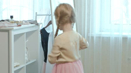 pigtail : cheerful little girl with pigtails in a pink skirt tries on mothers shoes on heels and dances in front of a mirror with a bag, mothers wardrobe Stock Footage
